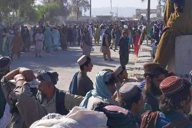 Aghan men stand on the street after Kabul fell to the Taliban