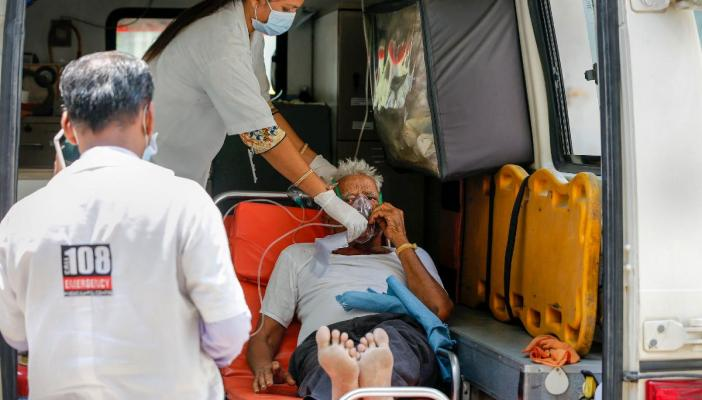 A COVID-19 patient is given an oxygen supply mask inside an ambulance outside the COVID-19 OPD of a government hospital in Ahmedabad