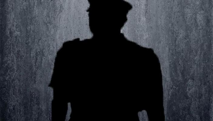 Shadow of a police officer against a grey background