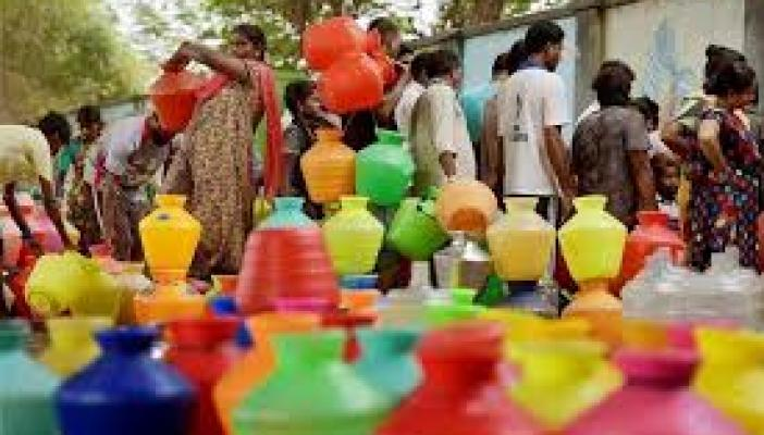 A coloured plastic pots in the image and women waiting to fill water in it.